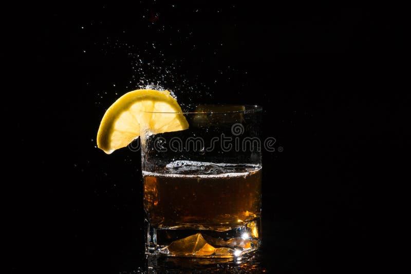Le verre de whiskey avec le citron et éclabousse sur le fond noir image stock
