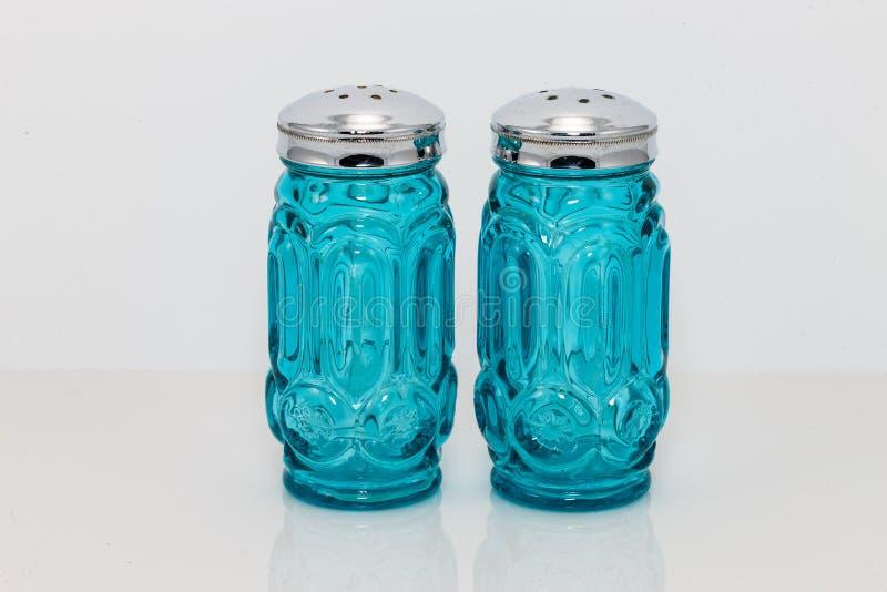 Le verre et l'argent bleus ont complété des dispositifs trembleurs de sel et de poivre photographie stock libre de droits