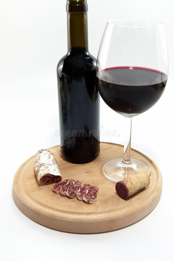 Le verre et la bouteille avec le vin rouge et sèchent le concept croustillant de luxe d'échantillon de vin de relaxation de salam photo stock