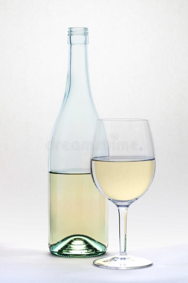 Le verre et la bouteille de vin blanc islolated sur le fond blanc photos stock