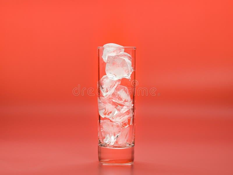 Le verre plein des glaçons sur le fond rose, se ferment vers le haut de la vue Les morceaux de l'eau solide en verre ont photogra photo libre de droits