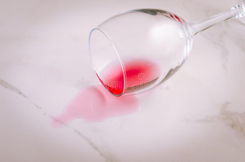 le verre tourné de vin rouge sur le fond de marbre/a versé le verre de vin rouge sur le fond de marbre photographie stock