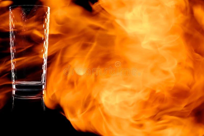 Le verre vide facetté de l'eau dans le feu flambe photographie stock libre de droits