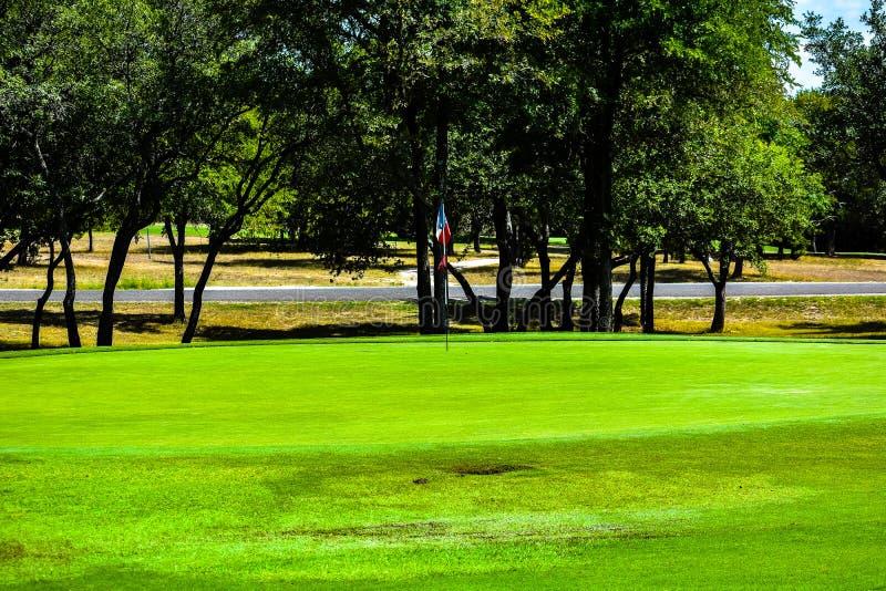 Le vert de golf dans le Texas central a garni des arbres avec un drapeau lonestar du Texas comme drapeau de golf images stock