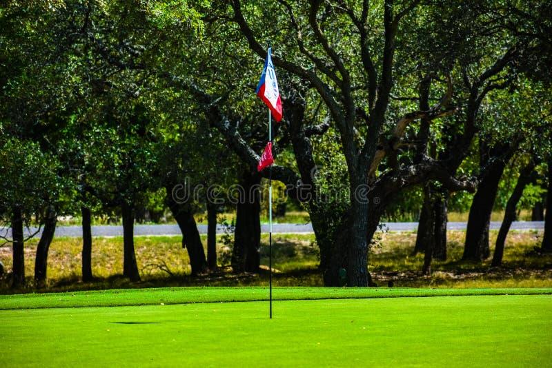 Le vert de golf dans le Texas central a garni des arbres avec un drapeau lonestar du Texas comme drapeau de golf photos libres de droits