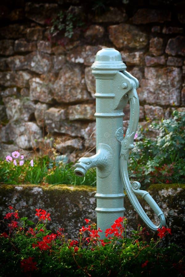 Le vert a peint la vieille pompe à eau au-dessus d'un puits photographie stock