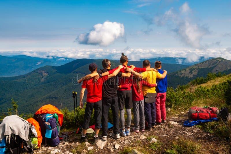 Le viandanti, amici stanno, abbracciando su una cima della montagna immagine stock