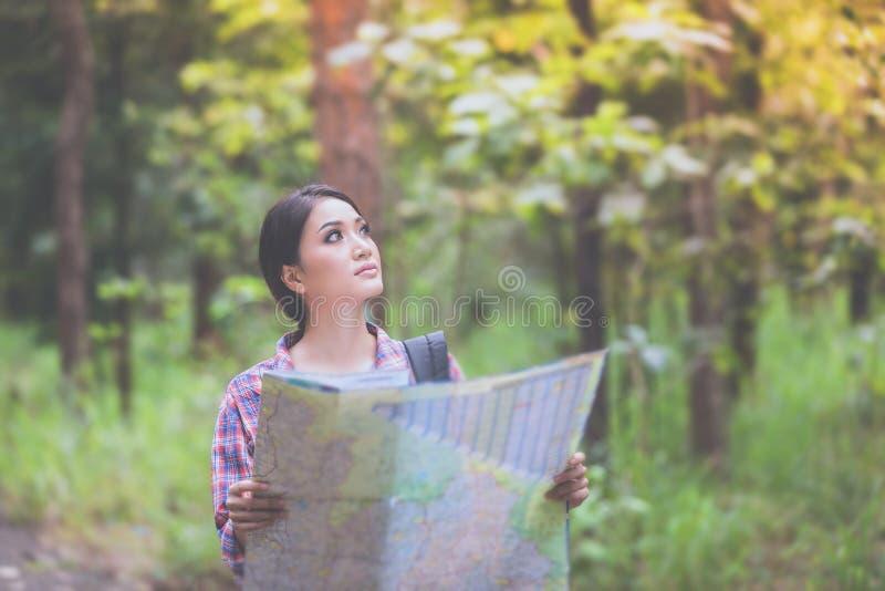 Le viandanti delle giovani donne che esaminano la mappa e si rilassano il tempo in vacanza concentrato fotografia stock