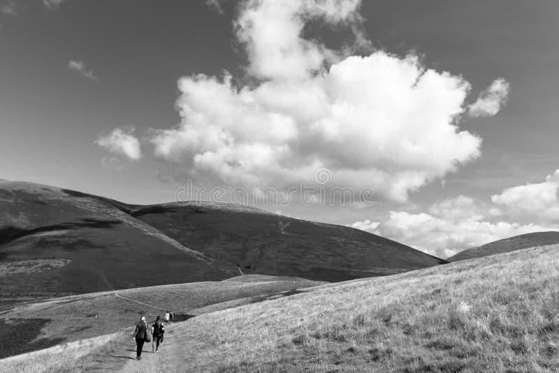 Le viandanti in Latrigg che trascura Keswick ed il lago Derwent innaffiano, Cu fotografia stock libera da diritti