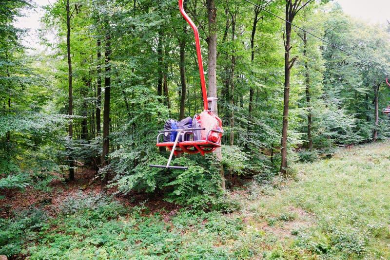 Le viandanti usano Ski Lift per trasferire pesante aumentano la marcia la montagna di estate fotografia stock libera da diritti