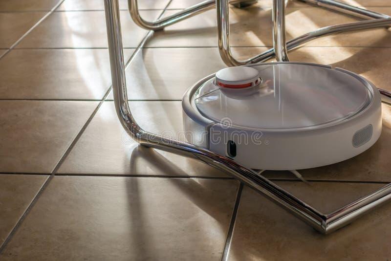 Le vide robotique moderne nettoie dans tous les coins photo stock