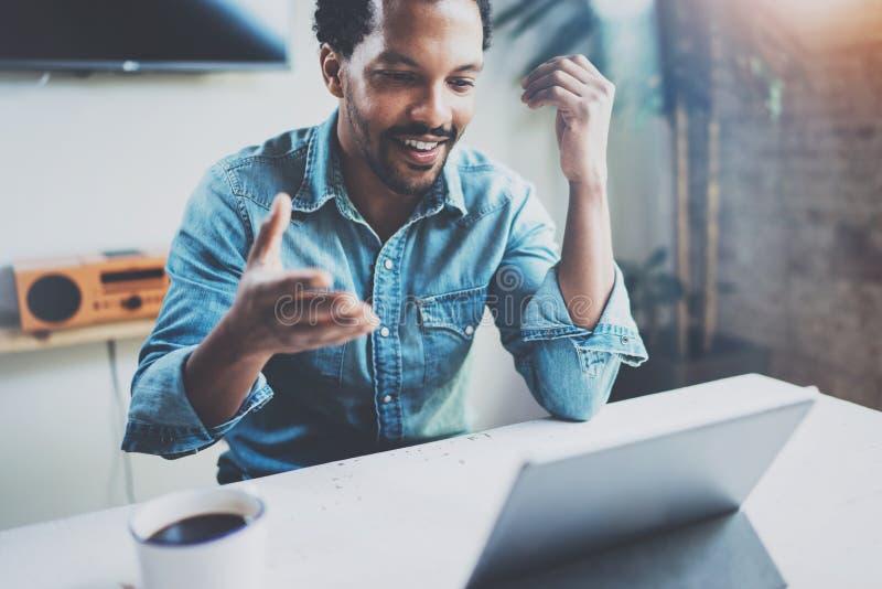 Le video konversation för ung afrikansk mandanande via den digitala minnestavlan med affärspartners, medan sitta i soligt arkivfoton