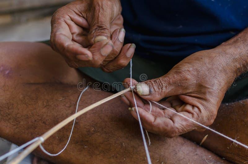 Le vieil homme attachant une corde pour font un cerf-volant photos stock