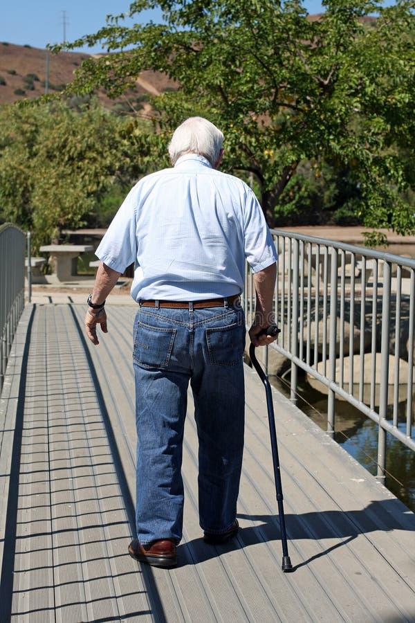 Le vieil homme avec une canne marche loin image stock