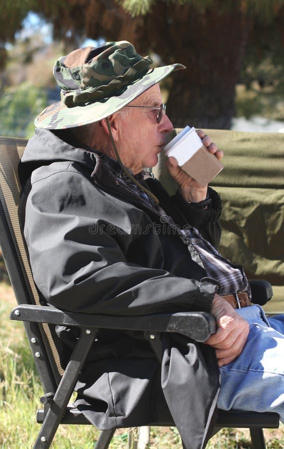Le vieil homme boit du café   photos stock