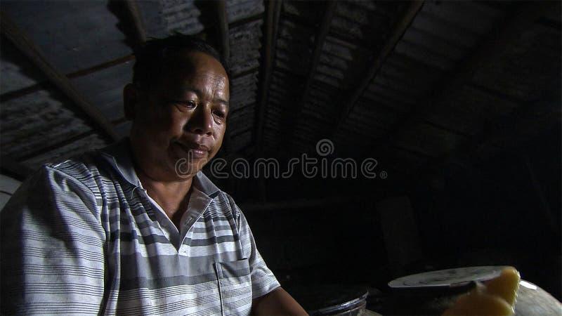 Le vieil homme chinois fait les pousses de bambou aigres pour préserver yunnan La Chine photographie stock