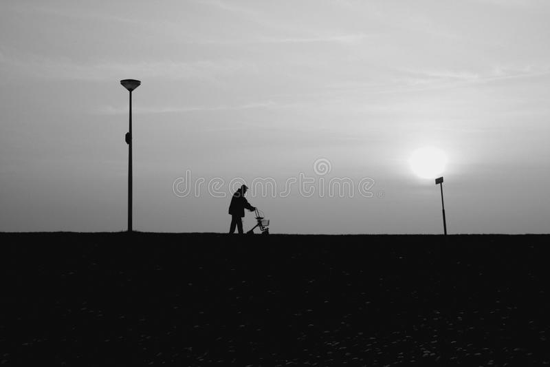 Le vieil homme marche avec son rollator au coucher du soleil photo stock