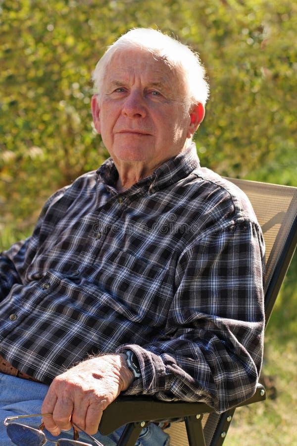 Le vieil homme observé bleu s'assied à l'extérieur image libre de droits