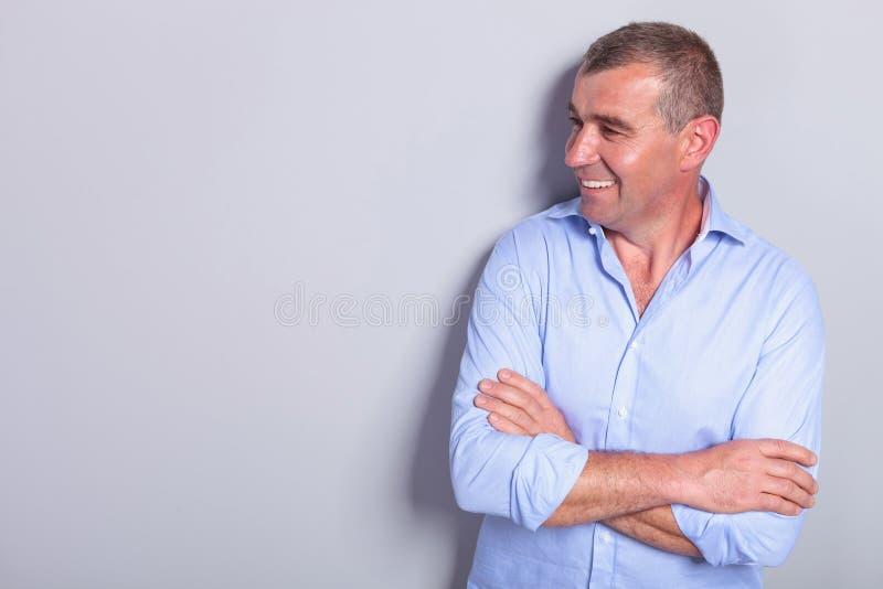 Le vieil homme occasionnel avec des bras pliés regarde pour dégrossir image stock
