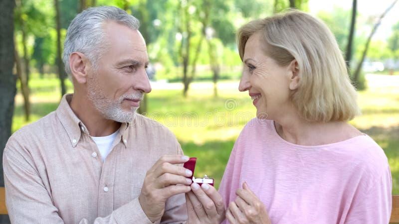Le vieil homme propose le mariage à la dame, renouvellement de serment sur l'anniversaire de mariage d'or photographie stock libre de droits