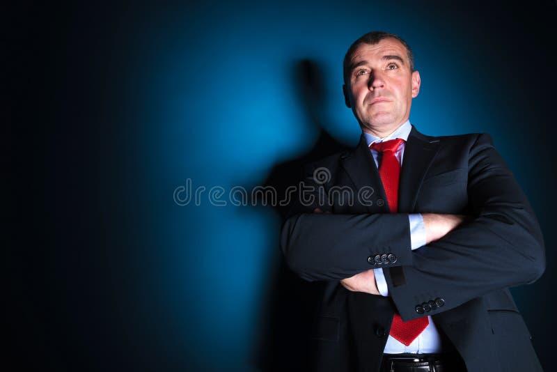 Le vieil homme sérieux d'affaires avec des bras a plié le regard loin photographie stock
