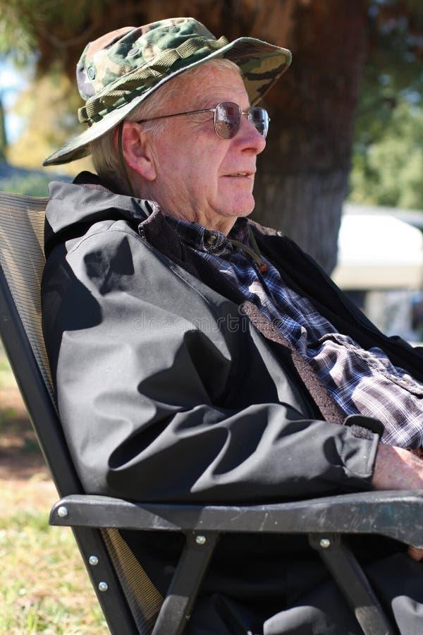 Le vieil homme s'assied à l'extérieur photo stock