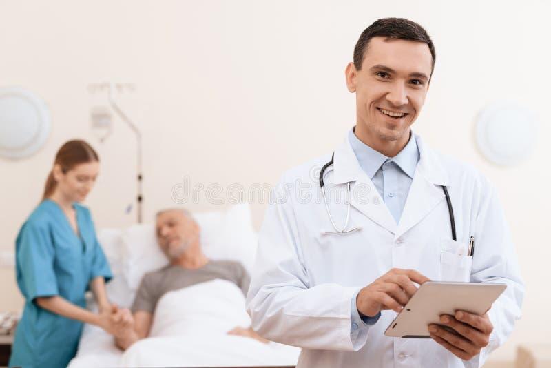 Le vieil homme se trouve sur un berceau dans la salle médicale, et à côté de lui il y a un médecin et une infirmière photos libres de droits
