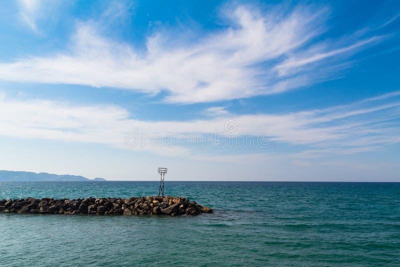 Le vieil observatoire rouillé sur l'estuaire de rivière menant à la vue de mer opacifie le ciel clair Grèce image stock