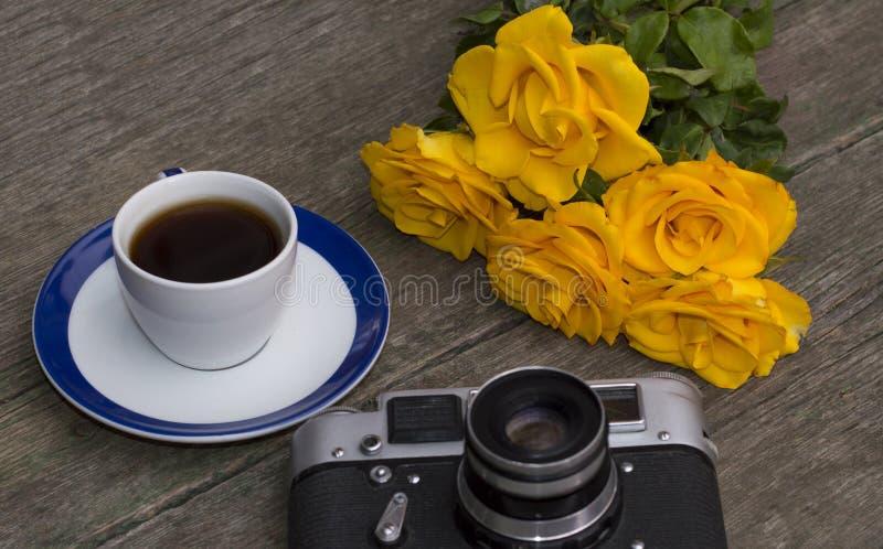 Le vieux appareil-photo, roses et café de film sur une table en bois image libre de droits