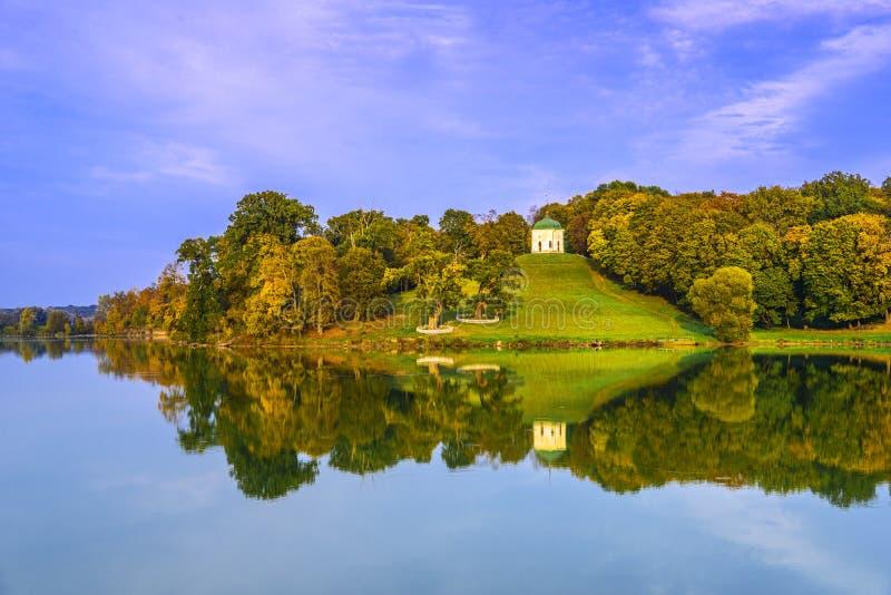 Le vieux bâtiment blanc entouré par des arbres d'automne s'est reflété dans le lac images libres de droits