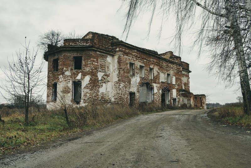 Le vieux bâtiment délabré effrayant près de la route et les arbres se développent photo libre de droits