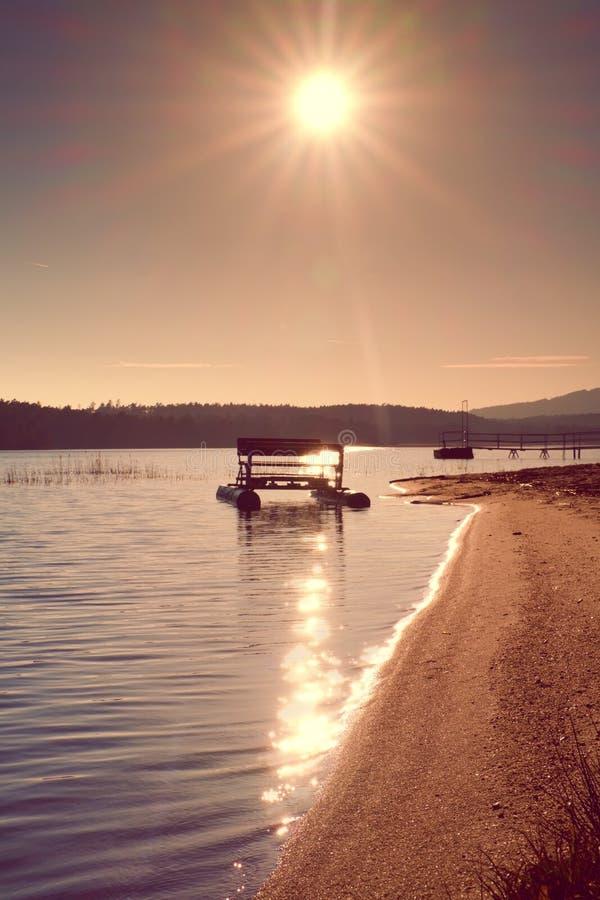 Le vieux bateau de palette rouillé abandonné a collé sur le sable de la plage Niveau d'eau onduleux, île sur l'horizon photos libres de droits
