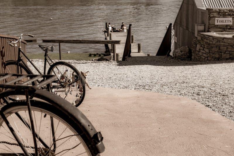 Le vieux bicyle roule dedans la rue dans la petite ville avec la jeunesse du groupe quatre dans la distance sur la jetée photo stock