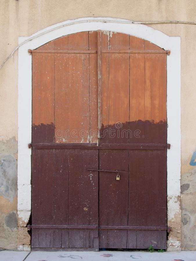 Le vieux brun de décomposition pittoresque a peint les portes à deux battants en bois boulonnées fermées avec un cadenas réglé da photo stock