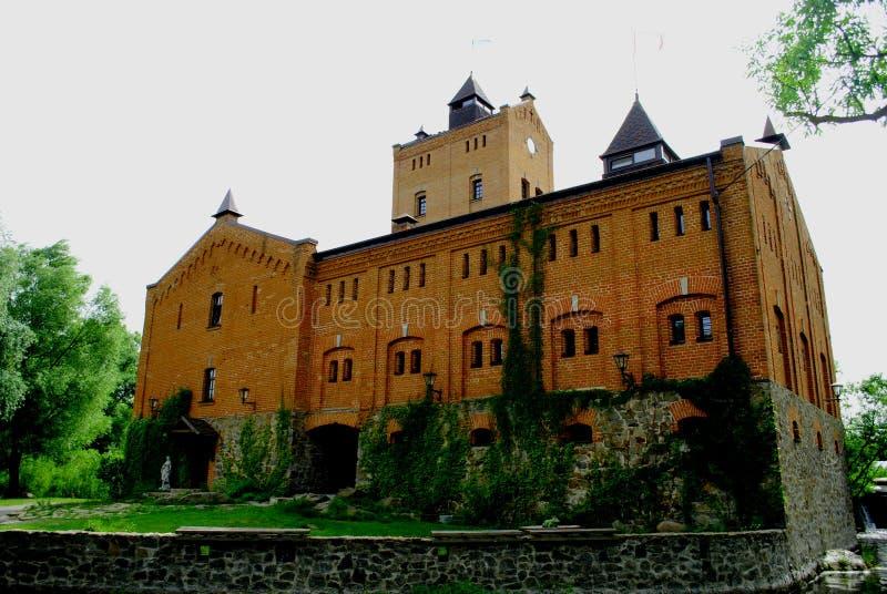 Le vieux château de brique entouré par le parc vert photo libre de droits