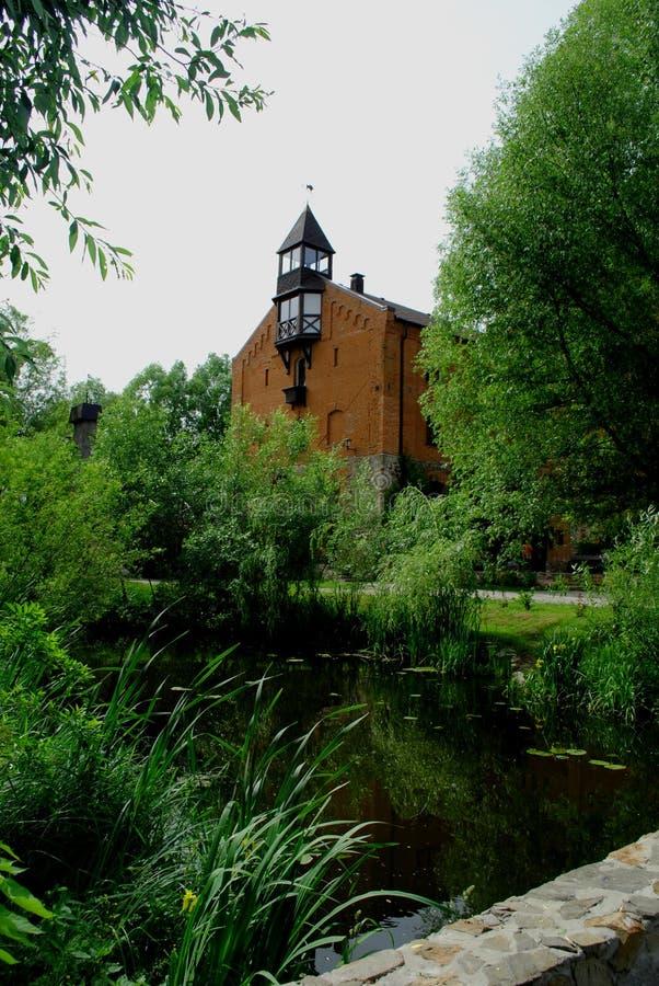 Le vieux château de brique entouré par le parc vert image stock