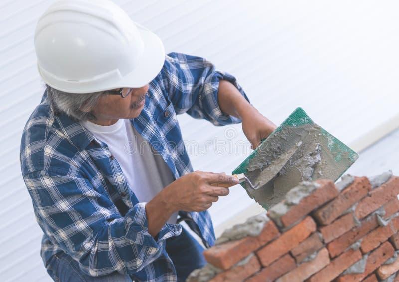 Le vieux constructeur nivelle le mur de briques image stock