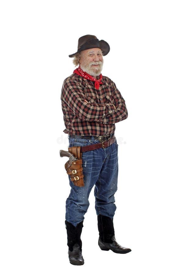 Le vieux cowboy de sourire reste avec des bras croisés photo stock