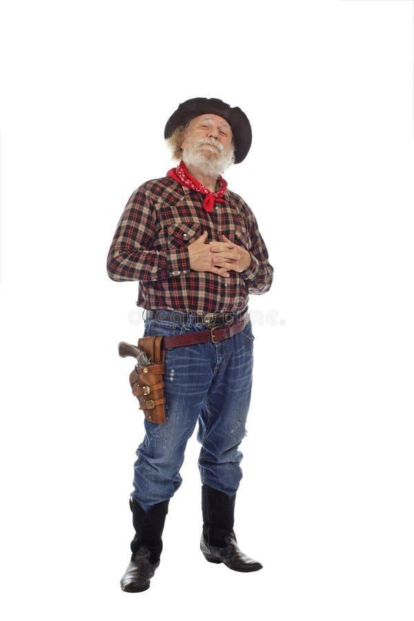 Le vieux cowboy occidental fier reste avec des mains étreintes photos libres de droits
