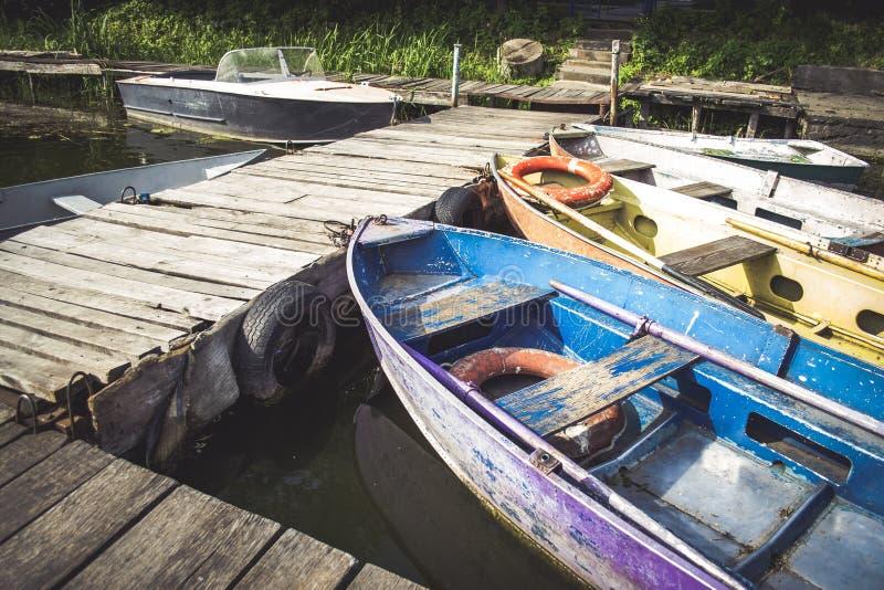 Le vieux fer a frangé et les nez minables de bateau ont attaché au dock en bois image stock