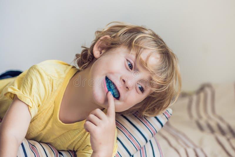 Le vieux garçon de trois ans montre que l'entraîneur myofonctionnel illuminait l'habitude de respiration de bouche Aides égaliser photo stock