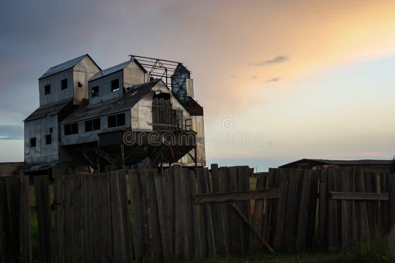 Le vieux grenier abandonné dans les rayons du coucher du soleil, comme un château mobile photos libres de droits