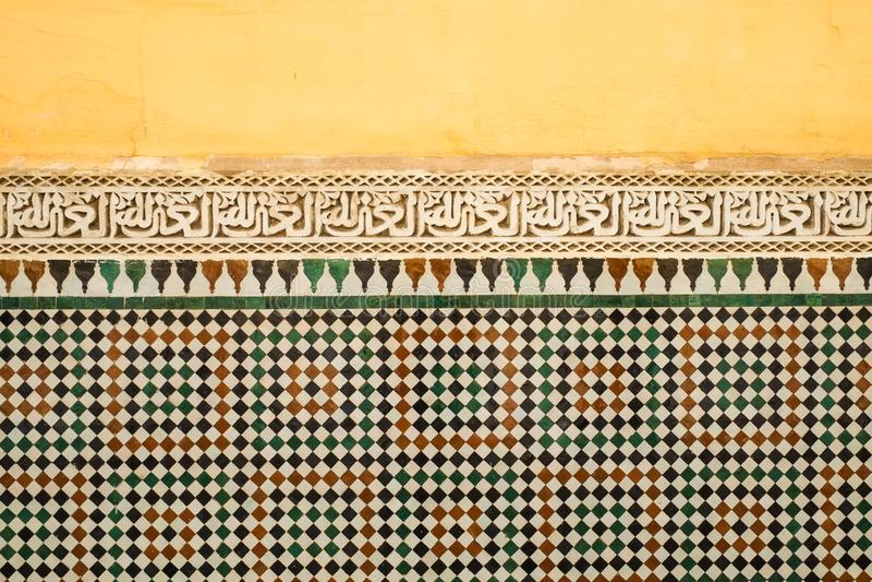Le vieux jaune marocain coloré a peint le mur avec une bande de la calligraphie islamique au-dessus du tilework de zellige images stock