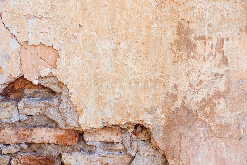 Le vieux jaune minable superficiel par les agents criqué peint a plâtré le fond épluché de mur de briques images libres de droits