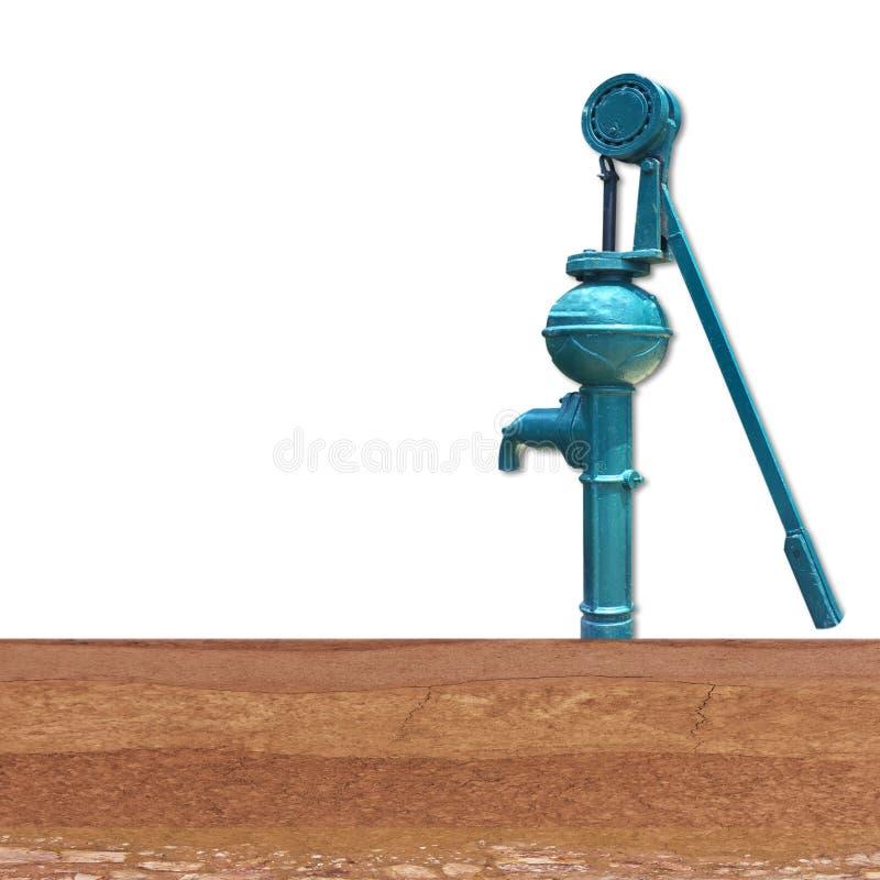 Le vieux levier manuel de pompe à eau pompe sur la couche de sol au fond image libre de droits