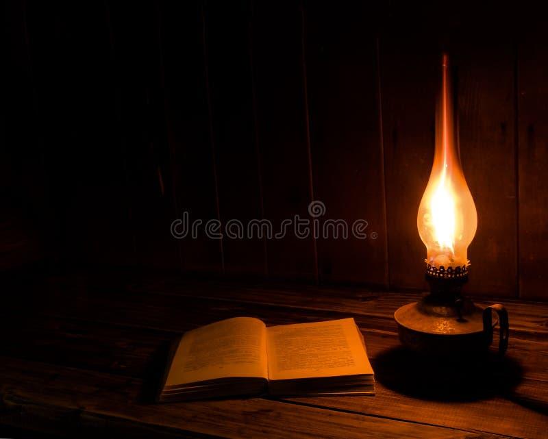 Le vieux livre antique s'est ouvert avec la lampe de kérosène brûlante photographie stock
