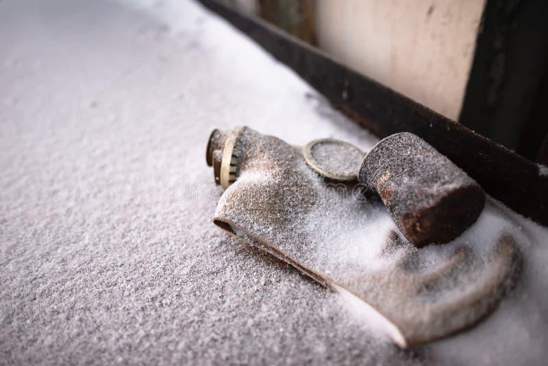 Le vieux masque à gaz soviétique lancé qui roule sous la neige imite la vie de Tchernobyl image stock