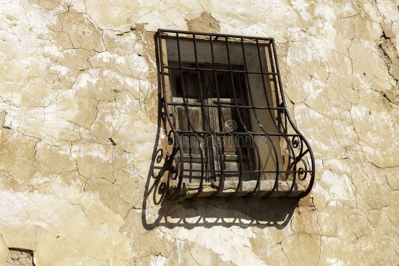 Le vieux mur avec éplucher la peinture, a rayé le plâtre de cru et la fenêtre avec la grille forgée par fer rouillé photographie stock