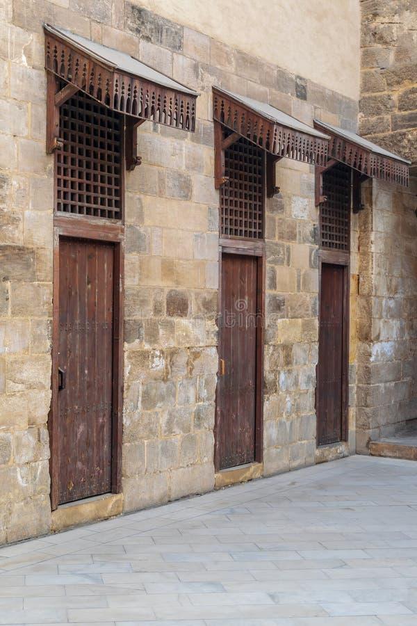 Le vieux mur de briques en pierre abandonné avec trois a survécu aux portes en bois couvertes de grille en bois photographie stock