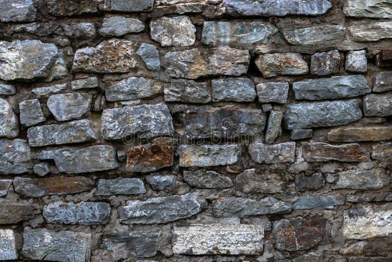 Le vieux mur en pierre est garni de la pierre de diverses nuances de gris et de brun images stock